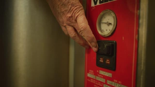 vidéos et rushes de la main d'une femme âgée transforme un brûleur commercial en retournant un commutateur dans une installation de cuisine/fabrication commerciale - température