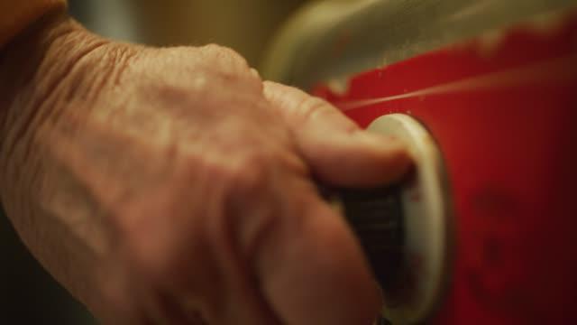 vídeos y material grabado en eventos de stock de la mano de una mujer mayor enciende un quemador comercial girando un dial en una instalación de cocina/fabricación comercial - dial