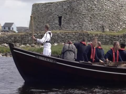 an olympic torchbearer holds the olympic torch in the bow of a boat. - flaming torch stock videos & royalty-free footage