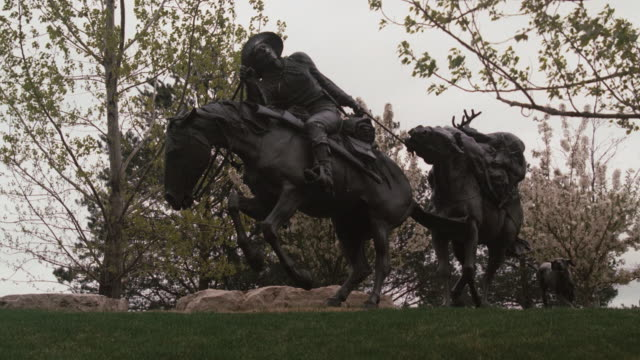 an omaha memorial depicts a cowboy with a deer carcass on his pack horse. - antler stock videos & royalty-free footage