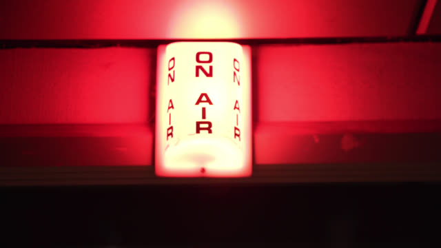 vídeos de stock, filmes e b-roll de an 'on air' lightbox flashes red in a recording studio - feito pelo homem