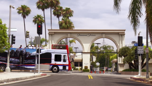 An open deck bus travels past the main gate of Paramount Studios in California.