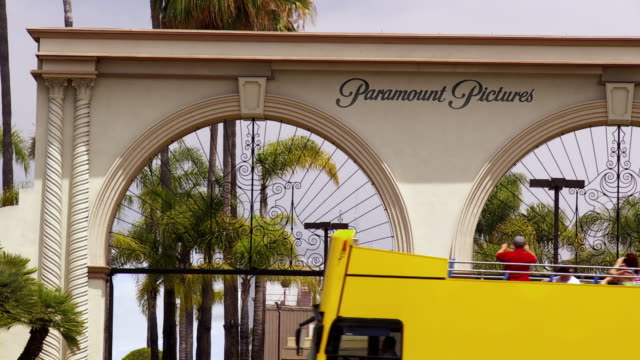an open deck bus travels past the main gate of paramount studios in california. - paramount studios stock videos & royalty-free footage