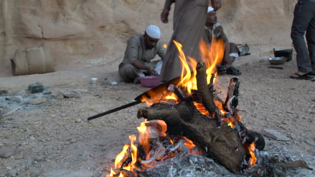 an open fire at a bedouin camp in wadi rum desert, jordan - ベドウィン族点の映像素材/bロール