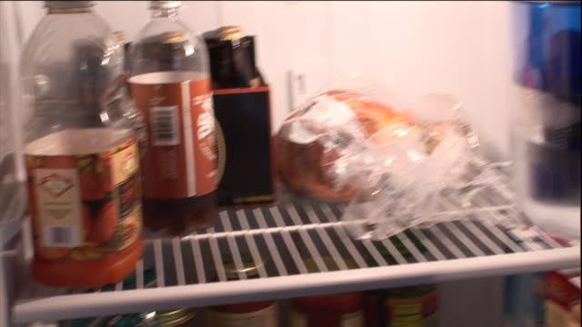 vidéos et rushes de an open refrigerator displays foods and beverages. - réfrigérateur