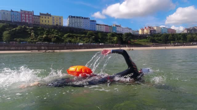 an open water swimmer passes the paddle boarder on september 18 in tenby, wales. open water swimming has become popular as a way of improving well... - wellbeing stock videos & royalty-free footage