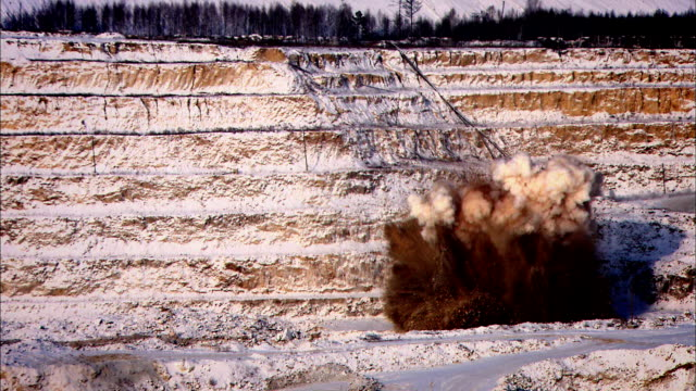 An opencast mine in Siberia uses blasting to excavate aggregates. Available in HD.