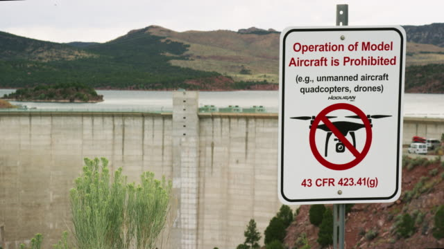 """an """"operation of model aircraft is prohibited"""" sign posted next to flaming gorge dam in utah on an overcast day - regole video stock e b–roll"""