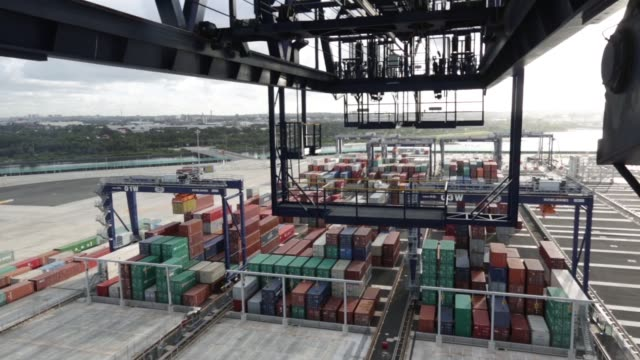 vídeos y material grabado en eventos de stock de an operator remotely controls an automated stacking crane to transport shipping containers at terminal 3 of port botany operated by sydney... - pórtico automotor