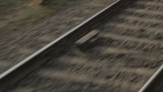 an optical illusion is created as neighbouring train tracks are filmed from the open door of a moving mumbai train, maharashtra, india. - bahngleis stock-videos und b-roll-filmmaterial