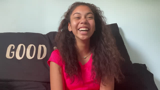 an optimistic african-american young girl laughs while in a zoom class from home - youth culture stock videos & royalty-free footage