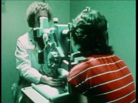 vidéos et rushes de an optometrist gives a patient an eye examination - opticien
