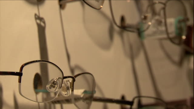 an optometrists's wall displays vision correction glasses. - eyesight stock videos & royalty-free footage
