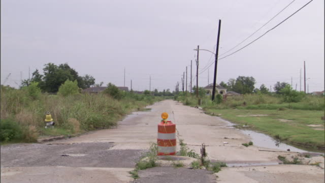 an orange barrel blocks traffic from a ruined, abandoned road following a flood in new orleans. - hurricane katrina stock videos and b-roll footage