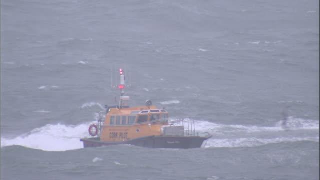 stockvideo's en b-roll-footage met an orange boat powers through a choppy sea. - rondrijden