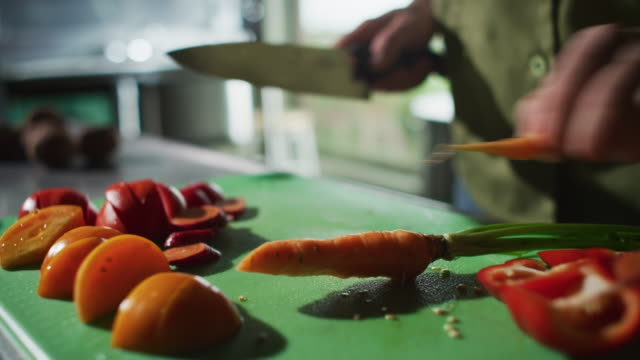 an orange carrot is sliced on a cutting board during meal preparation at a farm-to-table restaurant. - farm to table stock videos & royalty-free footage