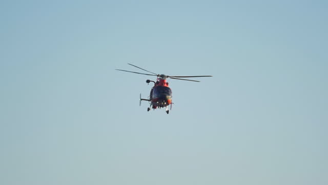 stockvideo's en b-roll-footage met an orange helicopter flies along the coast guard over the ocean. - slow motion - red sea