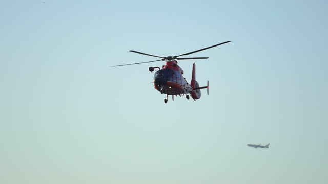 an orange helicopter flies along the coast guard over the ocean. - slow motion - safety stock videos & royalty-free footage