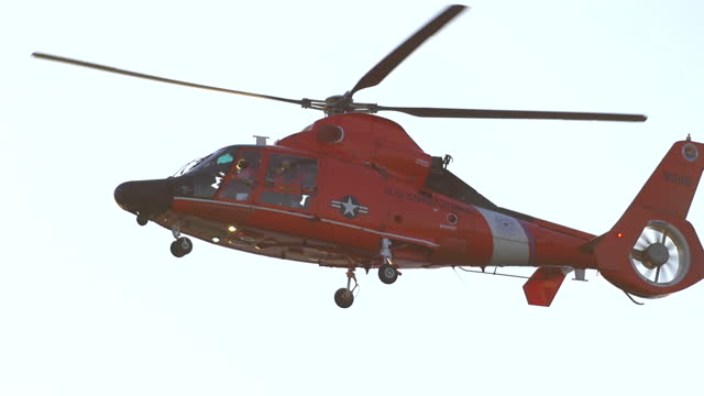an orange helicopter flies along the coast guard over the ocean. - slow motion - rescue stock videos & royalty-free footage
