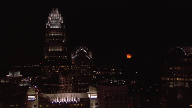an orange moon glows behind the skyline of downtown charlotte, north carolina. - charlotte north carolina stock videos & royalty-free footage