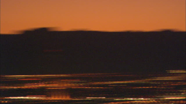 an orange sky glows above the twinkling lights of las vegas. - swish pan stock videos and b-roll footage