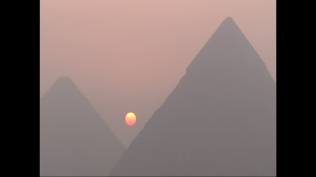 an orange sun glows through the smog between the great pyramids of giza. - air pollution stock videos & royalty-free footage