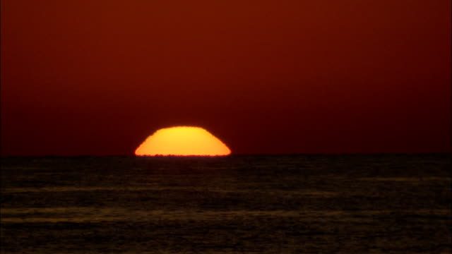 An orange sun slowly rises in a blood red sky over the Red Sea.\n Available in HD.