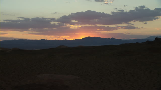 An orange sunset silhouettes mountains around Lake Mead.