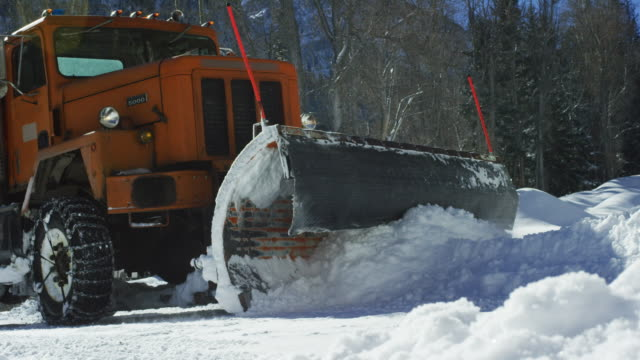 an orange tractor plows deep snow before disappearing behind a snowdrift next to a forest in the mountains in winter on a sunny day - snowplough stock videos & royalty-free footage