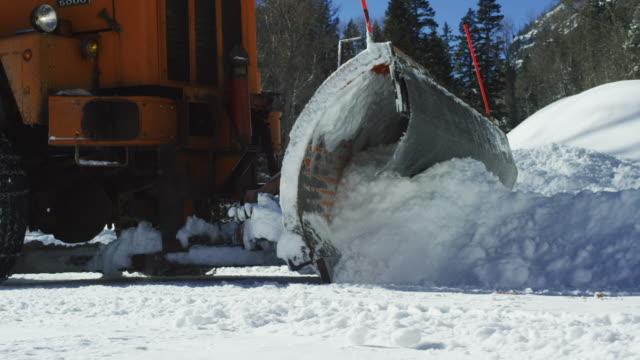 オレンジのトラクターは晴れた日に冬の山の森の横に深い雪を耕す - ユアレイ市点の映像素材/bロール