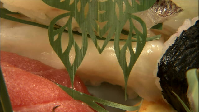 an orchid leaf cut into a butterfly pattern provides an unusual garnish. - nigiri stock videos and b-roll footage