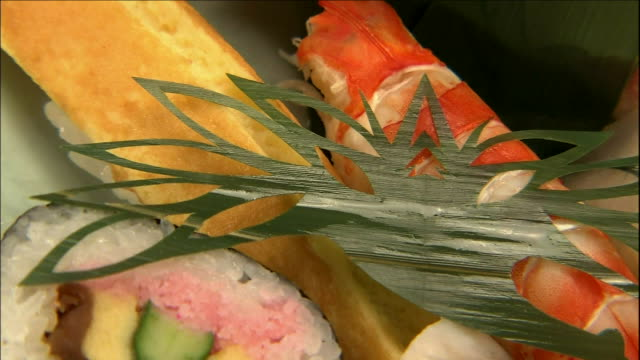 an orchid leave cut into a crane pattern provides an unusual garnish. - nigiri stock videos and b-roll footage