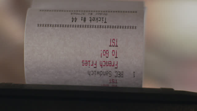 vidéos et rushes de slo mo. cu of an order ticket printing and a chef tearing it off from a receipt printer in a commercial kitchen - facture