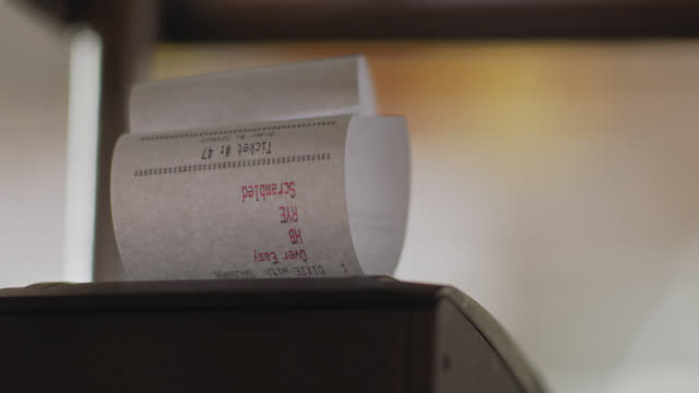 vidéos et rushes de cu of an order ticket printing from a receipt printer in a busy commercial kitchen - société de consommation