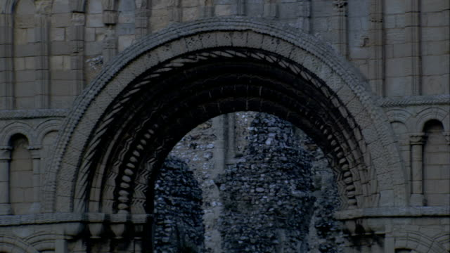 An ornate arch remains in the ruins of the Castle Acre Priory. Available in HD.