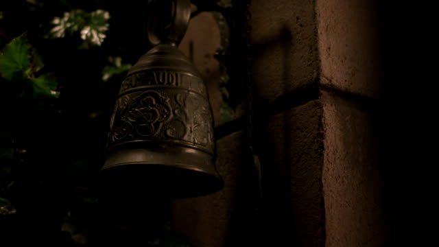 An ornate bronze bell hangs on a wall as a hand reaches up and pulls the chain to ring the bell.