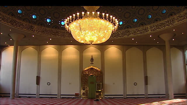 an ornate chandelier shines down on a large room in a mosque. - london central mosque stock videos & royalty-free footage