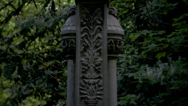 an ornate cross tops a tombstone in lawnswood cemetery. available in hd. - grabstein stock-videos und b-roll-filmmaterial