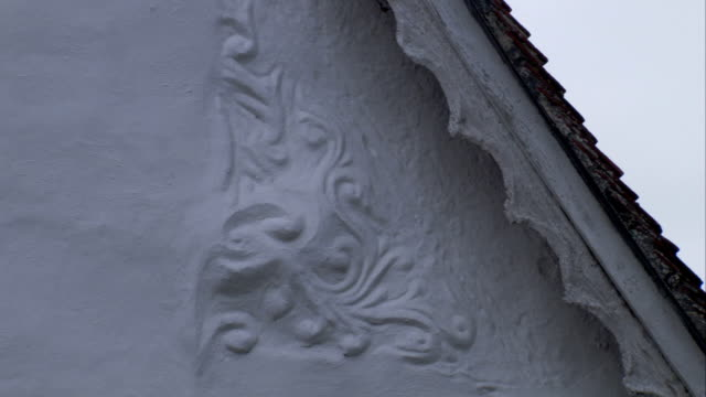 an ornate imprinted pattern adorns part of the exterior of a medieval cottage. available in hd. - lavenham stock-videos und b-roll-filmmaterial