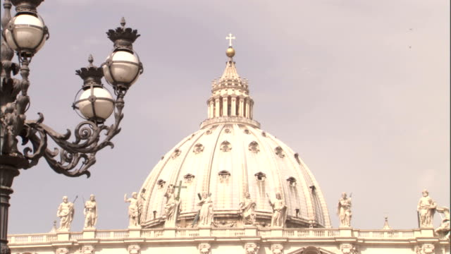 an ornate lamppost frames the dome of st. peter's basilica in vatican city. - basilica video stock e b–roll