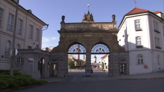 an ornate security gate at the pilsner urquell brewery controls access. - pilsner stock videos & royalty-free footage