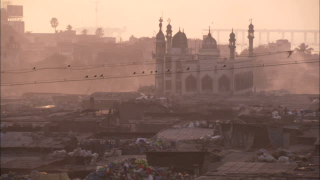 vidéos et rushes de an ornate temple towers behind the squalid slums of dharavi. available in hd. - inde