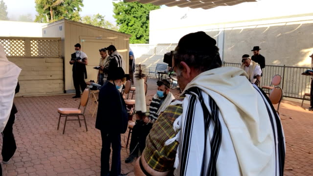 vídeos y material grabado en eventos de stock de an orthodox jewish congregation performs the weekday morning prayer service using covid safe procedures including masks and social distancing. a man... - torah