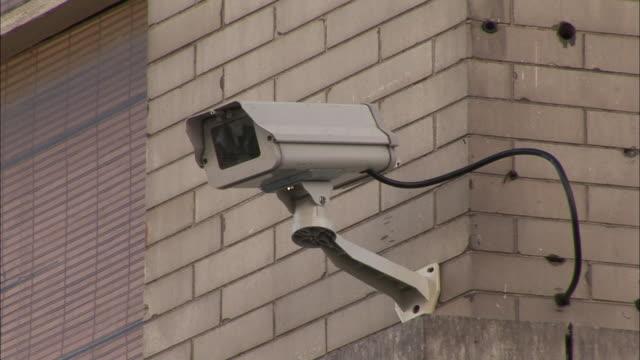 vidéos et rushes de an outdoor video surveillance camera is hard-wired to a brick building. - sécurité