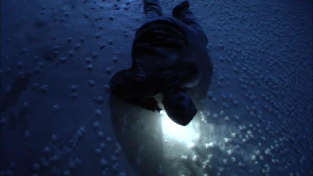 an outdoorsman carries a flashlight as he crawls over ice at night. - überleben stock-videos und b-roll-filmmaterial