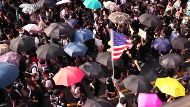 an overhead establishing shot of a protester waving an american flag in hong kong. - hong kong flag stock videos & royalty-free footage
