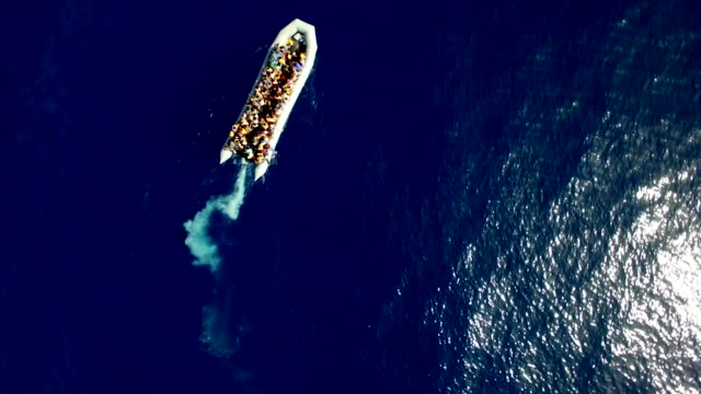 an overhead of a migrant boat slowly moving towards dry land off the italian coast in 2017 - flüchtling stock-videos und b-roll-filmmaterial