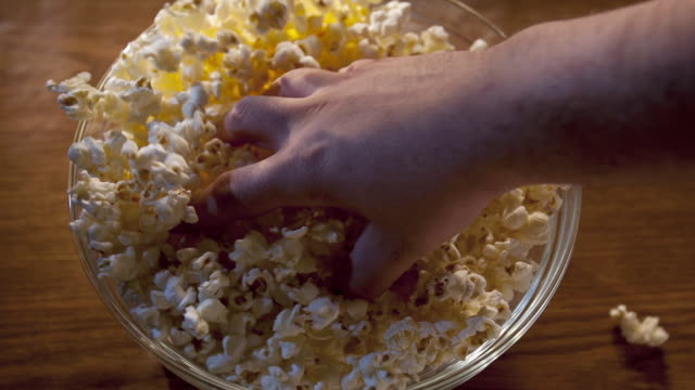 an overhead shot of a popcorn bowl with a hand diving in for popcorn. - popcorn stock videos & royalty-free footage