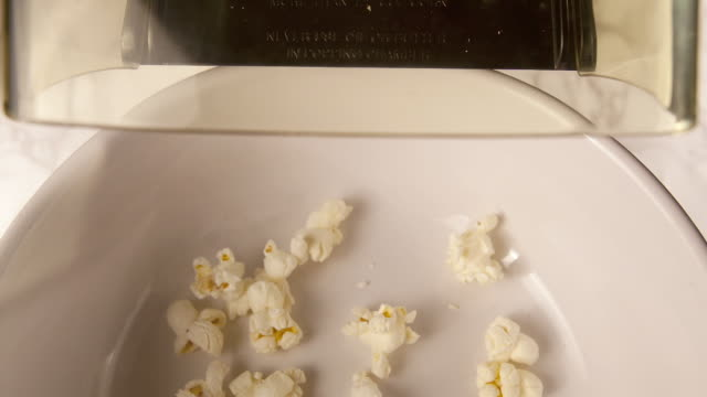 an overhead shot of popcorn exiting a machine onto a white bowl. - popcorn stock-videos und b-roll-filmmaterial