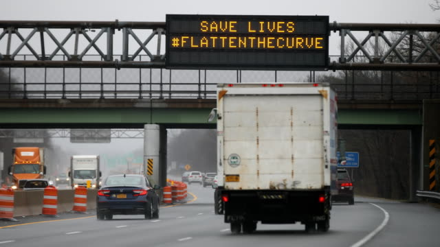 """an overhead sign on the seaford-oyster bay expressway informs drivers to """"stay home - stop the spread"""" and """"save lives #flattenthecurve"""" is seen as... - home economics点の映像素材/bロール"""